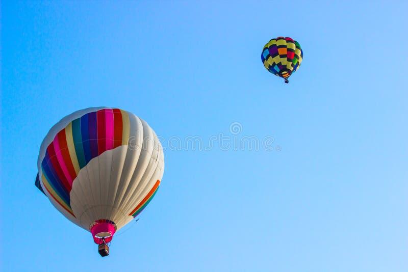 Dos globos coloreados multi del aire caliente en madrugada imagen de archivo