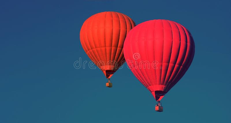 Dos globos rojos en el cielo aerostato Gente en la cesta Diversión Entretenimiento del verano Aventuras románticas Foto entonada  fotografía de archivo