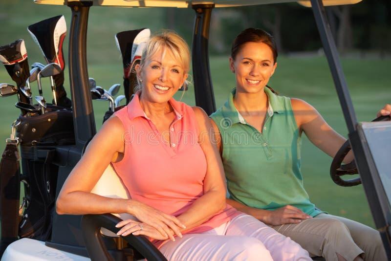 Dos golfistas femeninos que montan en cochecillo del golf fotos de archivo libres de regalías