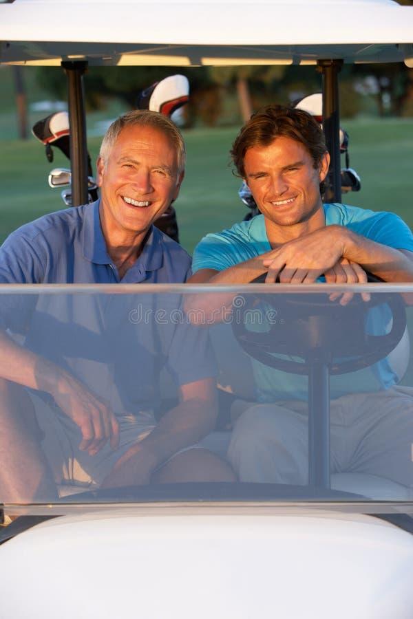 Dos golfistas masculinos que montan en cochecillo del golf fotografía de archivo libre de regalías