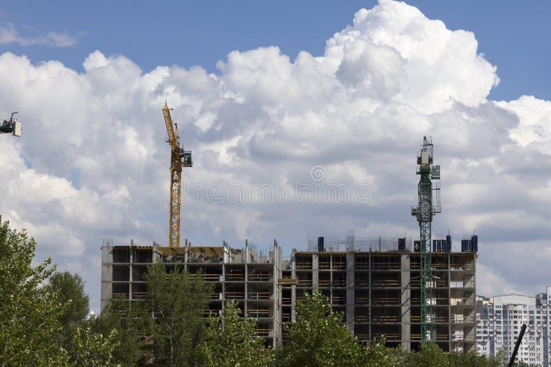 Dos grúa amarillos de la construcción contra el cielo azul fotos de archivo