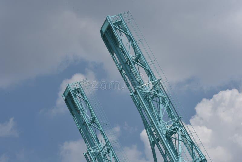 Dos grúas contra un cielo azul con las nubes foto de archivo libre de regalías