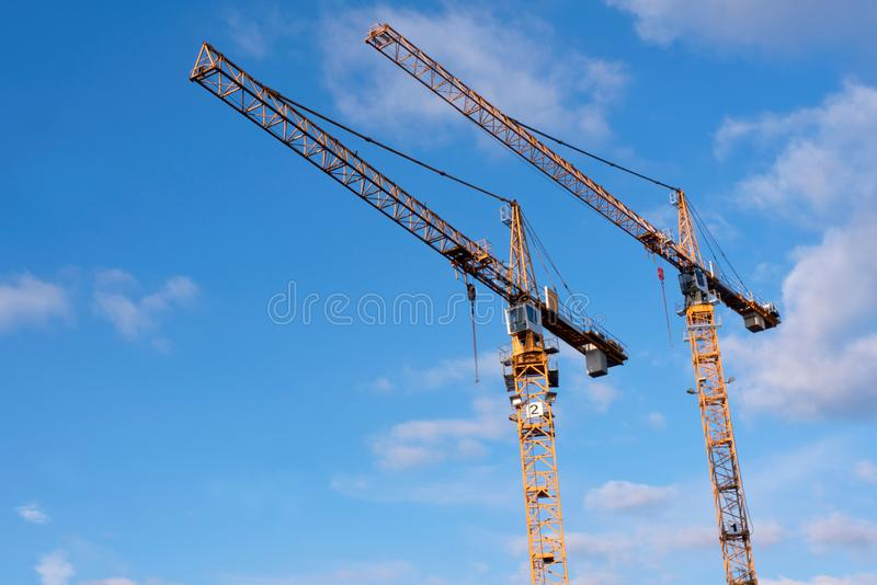 Dos grúas de construcción amarillas contra el cielo azul con algunos se nublan fotos de archivo