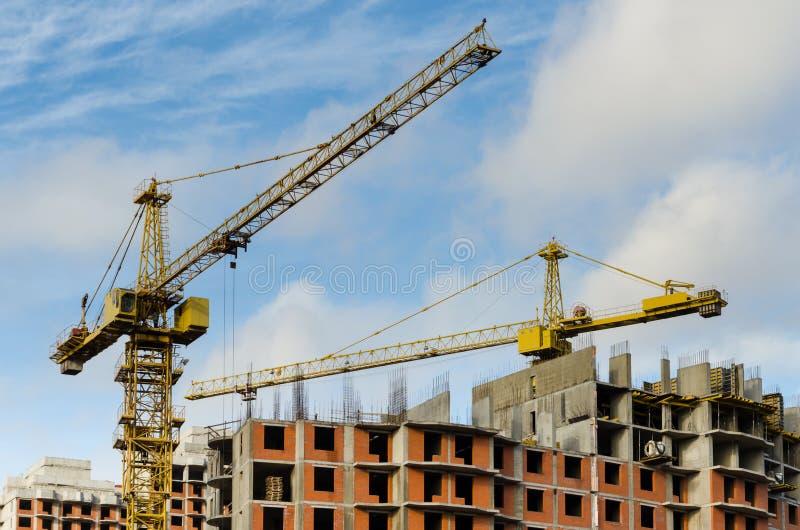 Dos gr?as de construcci?n amarillas en el emplazamiento de la obra de las casas de varios pisos del ladrillo contra el cielo azul imagen de archivo