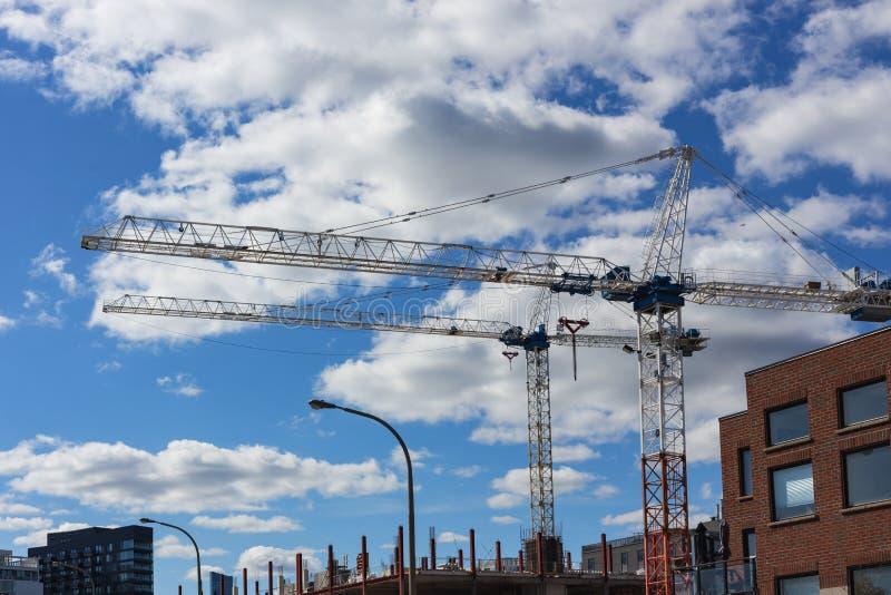 Dos grúas en las nubes del cielo azul del emplazamiento de la obra imagenes de archivo