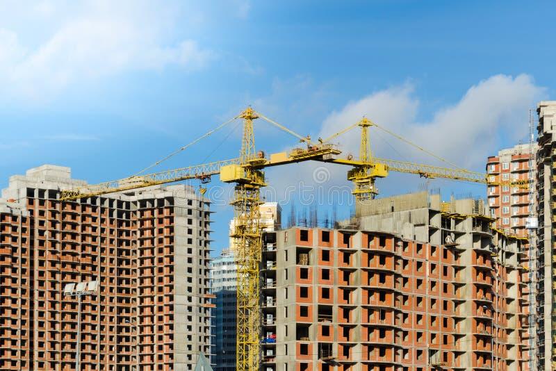 Dos gr?as de construcci?n amarillas en el emplazamiento de la obra de las casas de varios pisos del ladrillo contra el cielo azul foto de archivo libre de regalías