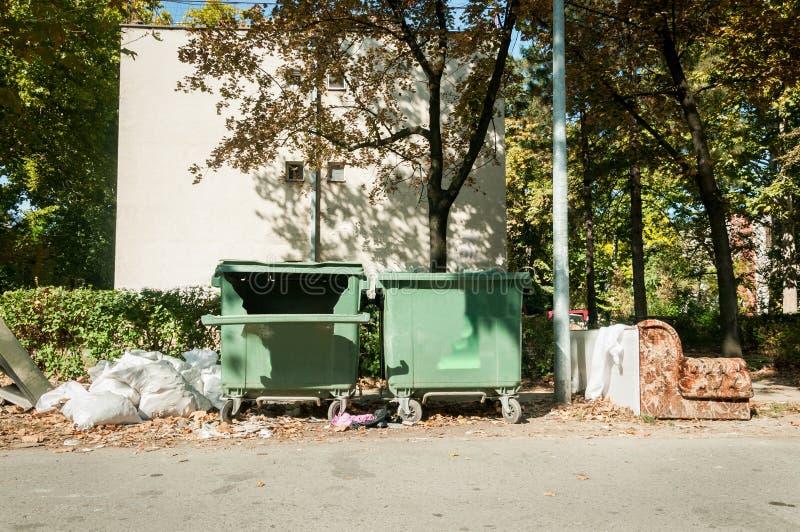 Dos grandes dañados y cubos de la basura plásticos rotos del contenedor por completo de litera del desbordamiento que contamina l foto de archivo