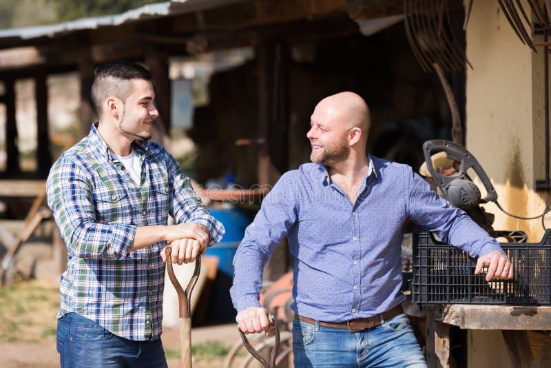Dos granjeros de sexo masculino en el corral foto de archivo