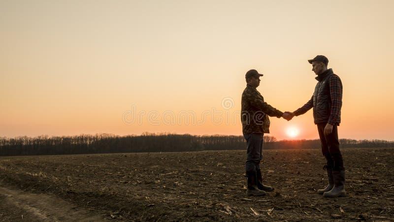 Dos granjeros en las manos de la sacudida del campo en la puesta del sol Tiro ancho de la lente imágenes de archivo libres de regalías