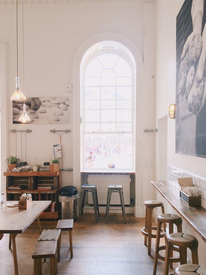 Dos Grey Wooden Stools Near Window con el marco del arco imagen de archivo libre de regalías
