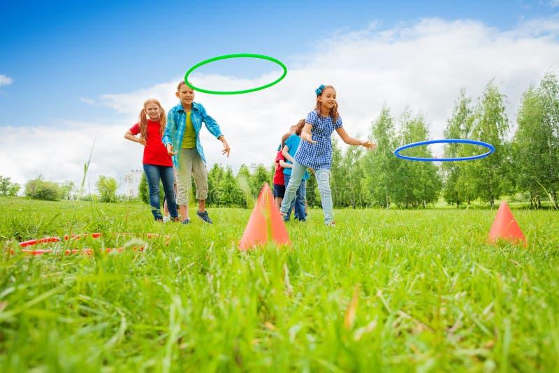 Dos grupos de juego de los niños que lanzan aros coloridos imagen de archivo