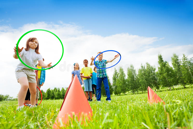 Dos grupos de niños que juegan con los aros del hula foto de archivo libre de regalías