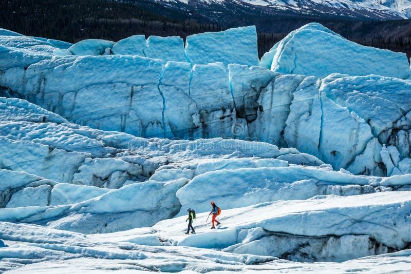 Dos guías del glaciar que caminan entre hendiduras y seracs grandes encima del glaciar de Matanuska en Alaska imagen de archivo