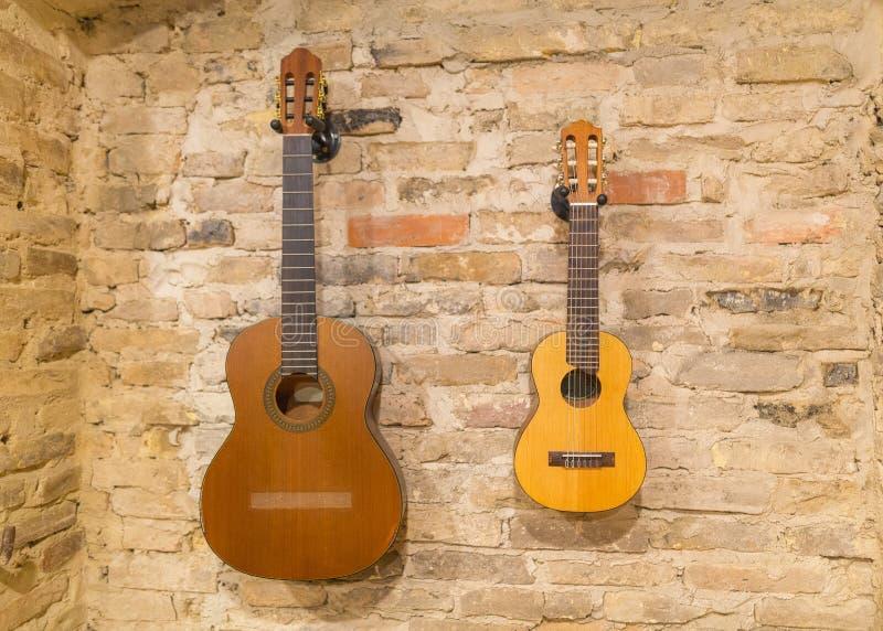 Dos guitarras acústicas que cuelgan en fondo de la pared de ladrillo dentro V fotografía de archivo