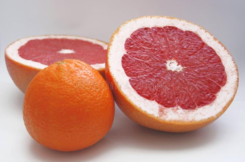 Dos halfs de la fruta de la uva roja y de una naranja imagen de archivo libre de regalías