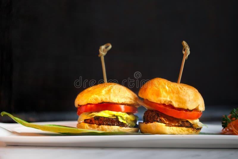 Dos hamburguesas contra un fondo negro llano fotografía de archivo