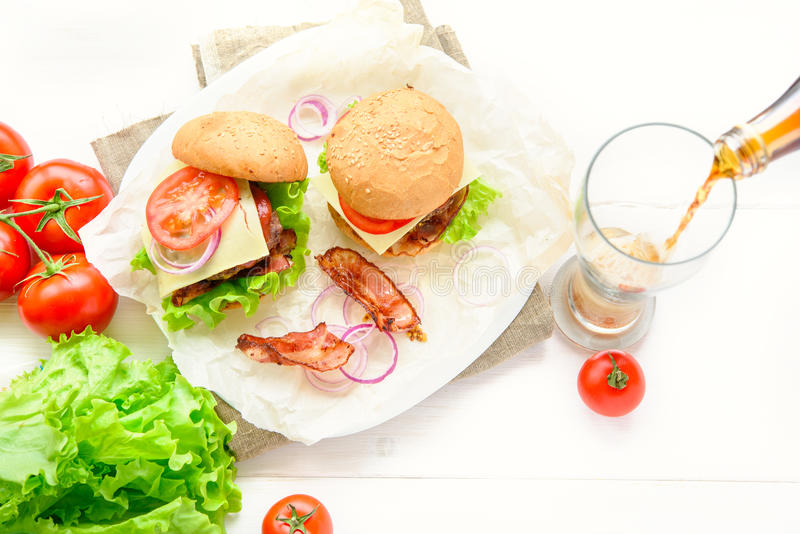 Dos hamburguesas sirvieron con el vidrio de soda de la cola en la tabla blanca fotografía de archivo libre de regalías