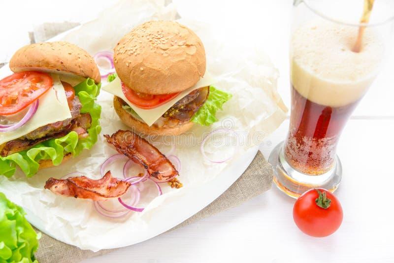 Dos hamburguesas sirvieron con el vidrio de soda en la tabla blanca fotografía de archivo