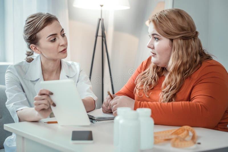 Dos hembras jovenes que hablan de dietas útiles imagenes de archivo