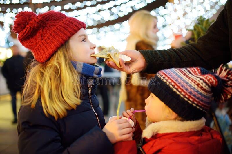 Dos hermanas adorables que beben el chocolate caliente y que comen las crepes del chocolate en mercado tradicional de la Navidad foto de archivo