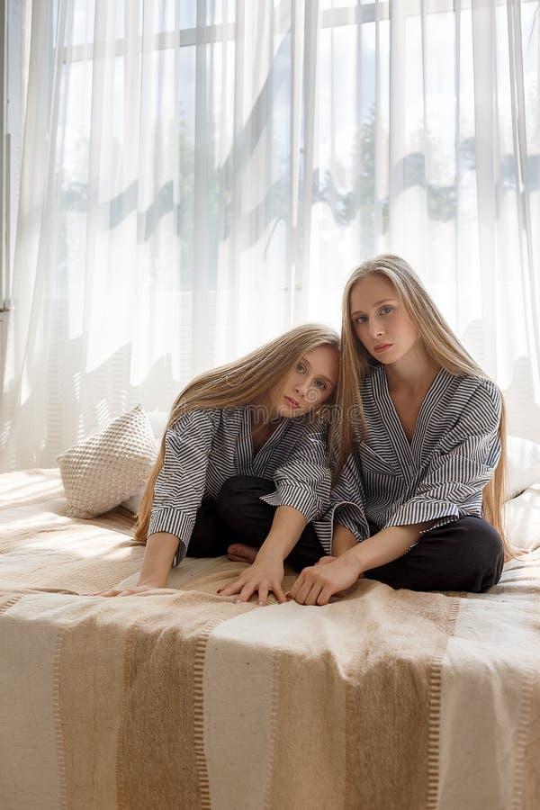 Dos hermanas bastante gemelas en vaqueros negros y camisas rayadas con el pelo largo que se sienta en el sofá contra el fondo de  fotos de archivo libres de regalías