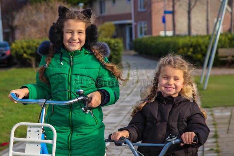 Dos hermanas de las muchachas montan las bicicletas Los niños holandeses gozan el completar un ciclo de cada día foto de archivo libre de regalías