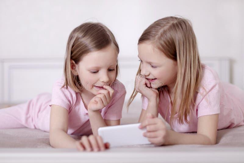 Dos hermanas de las niñas en pijamas rosados en la cama que miran un smartphone y que leen un eBook imagen de archivo libre de regalías