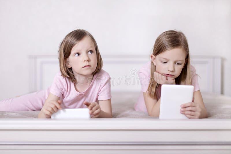 Dos hermanas de las niñas en pijamas rosados en la cama que miran un smartphone y que leen un eBook imagen de archivo