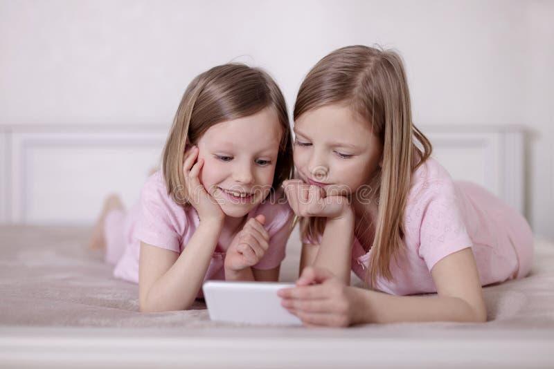 Dos hermanas de las niñas en pijamas rosados en la cama que miran un smartphone y que leen un eBook fotos de archivo libres de regalías