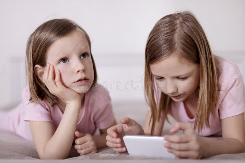 Dos hermanas de las niñas en pijamas rosados en la cama que miran un smartphone y que leen un eBook imágenes de archivo libres de regalías