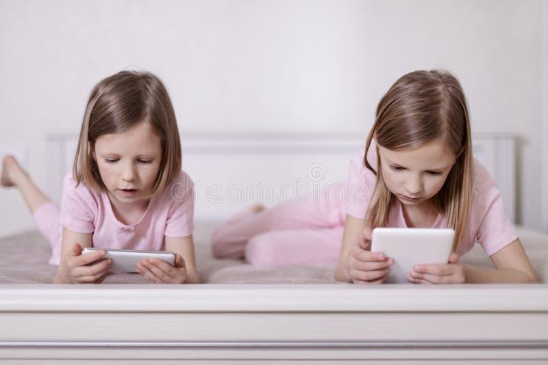 Dos hermanas de las niñas en pijamas rosados en la cama que miran un smartphone y que leen un eBook foto de archivo