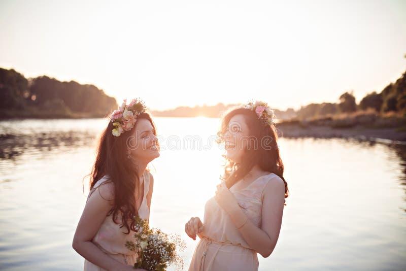 Dos hermanas de risa hermosas en los rayos de la puesta del sol foto de archivo libre de regalías