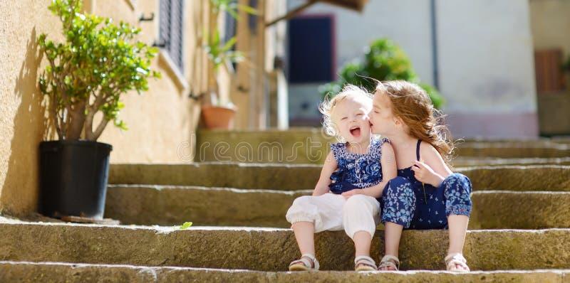 Dos hermanas del niño que se sientan en las escaleras en ciudad italiana imagenes de archivo