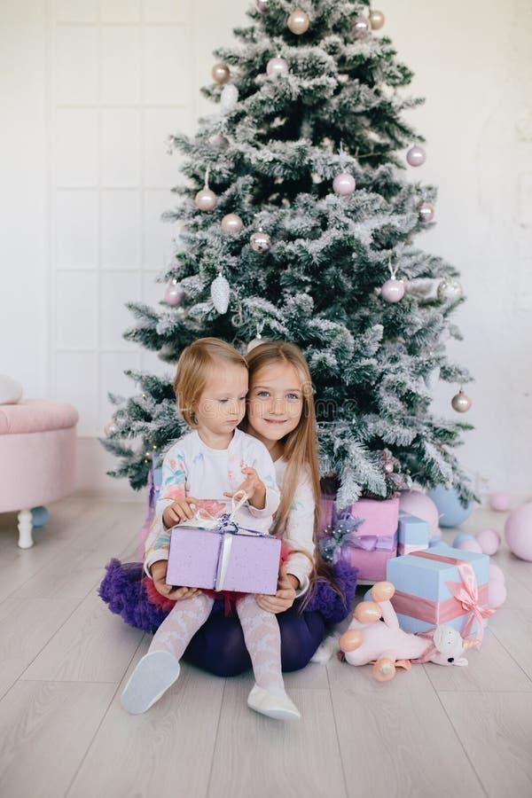 Dos hermanas en casa con el árbol de navidad y los presentes Muchachas felices de los niños con las cajas y las decoraciones de r foto de archivo libre de regalías