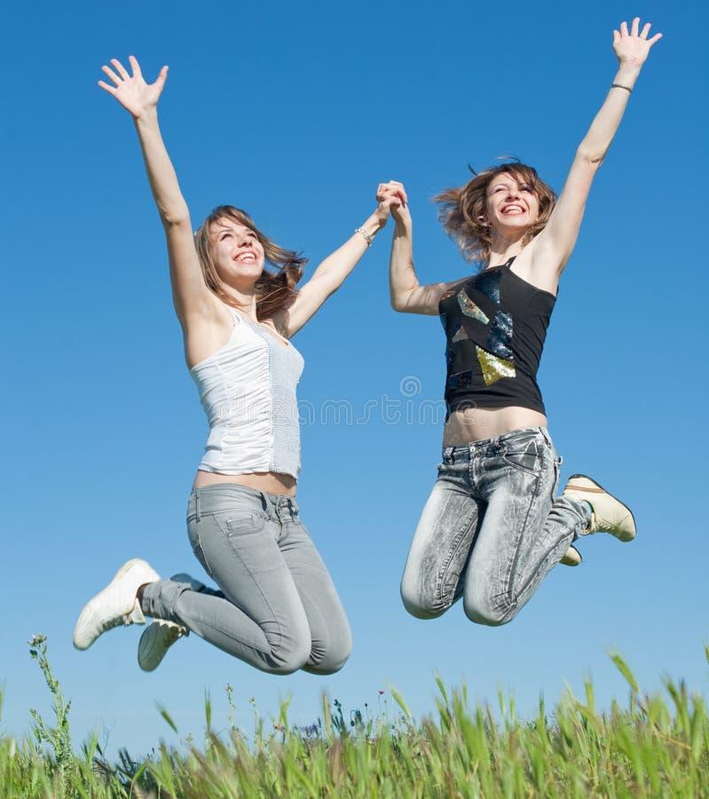Dos hermanas en los pantalones vaqueros que saltan al aire libre imágenes de archivo libres de regalías