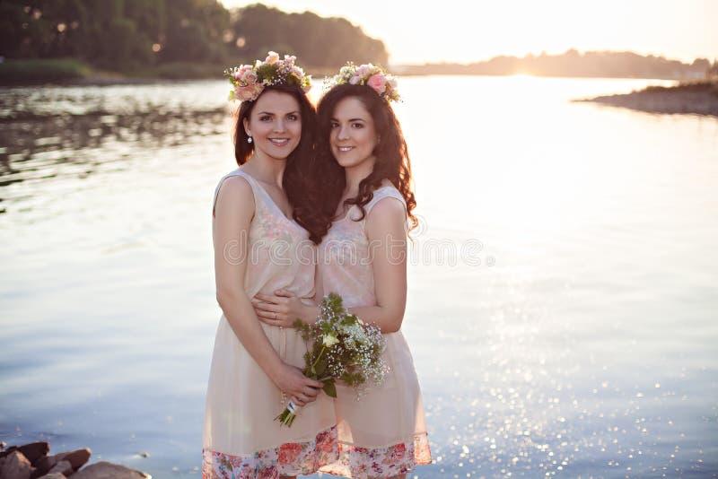 Dos hermanas en los rayos de la puesta del sol fotografía de archivo libre de regalías