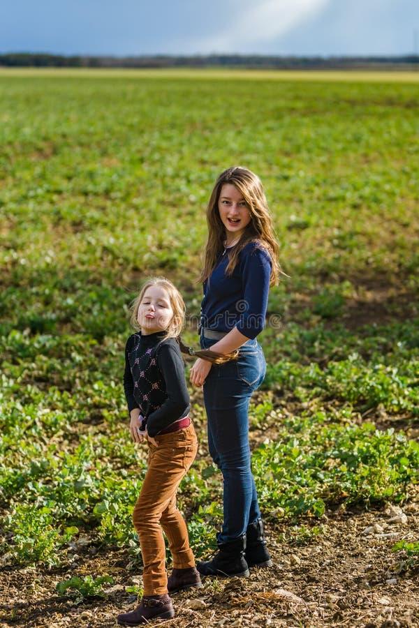 Dos hermanas felices con la naturaleza, primavera en el campo foto de archivo