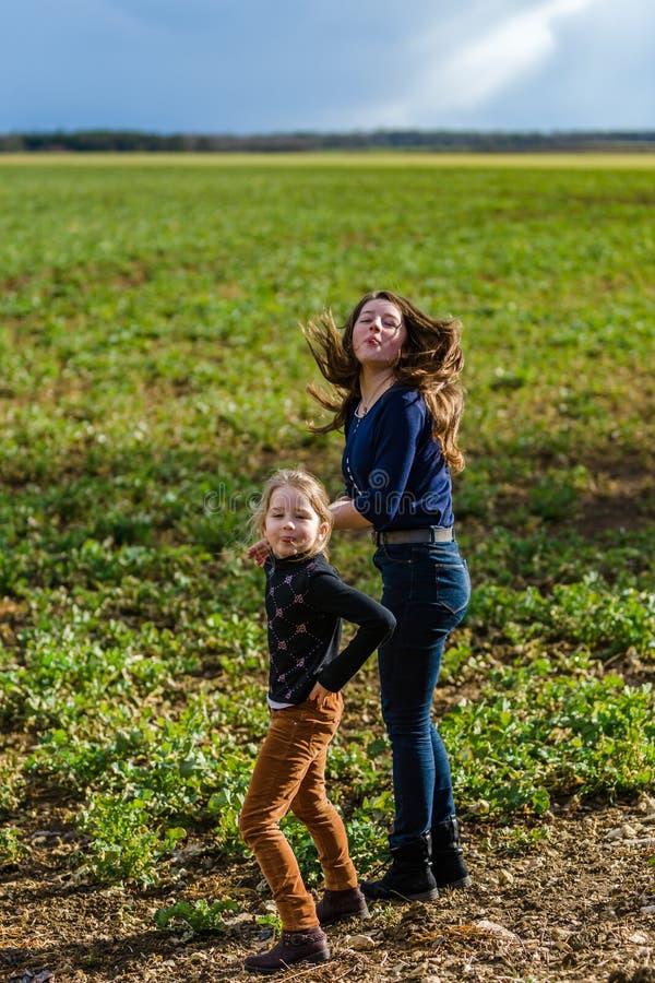 Dos hermanas felices con la naturaleza, primavera en el campo imagenes de archivo