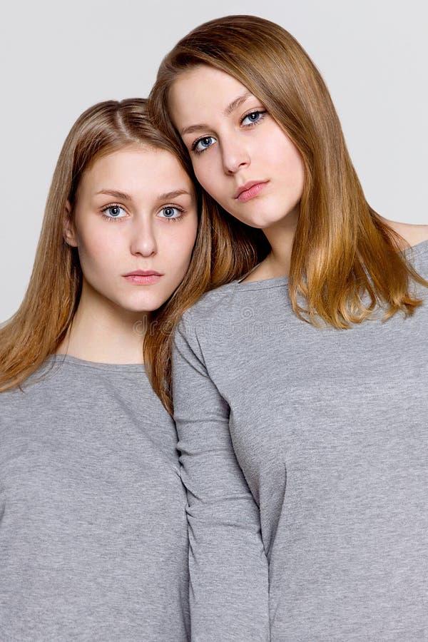 Dos hermanas gemelas acurrucadas, retrato foto de archivo libre de regalías
