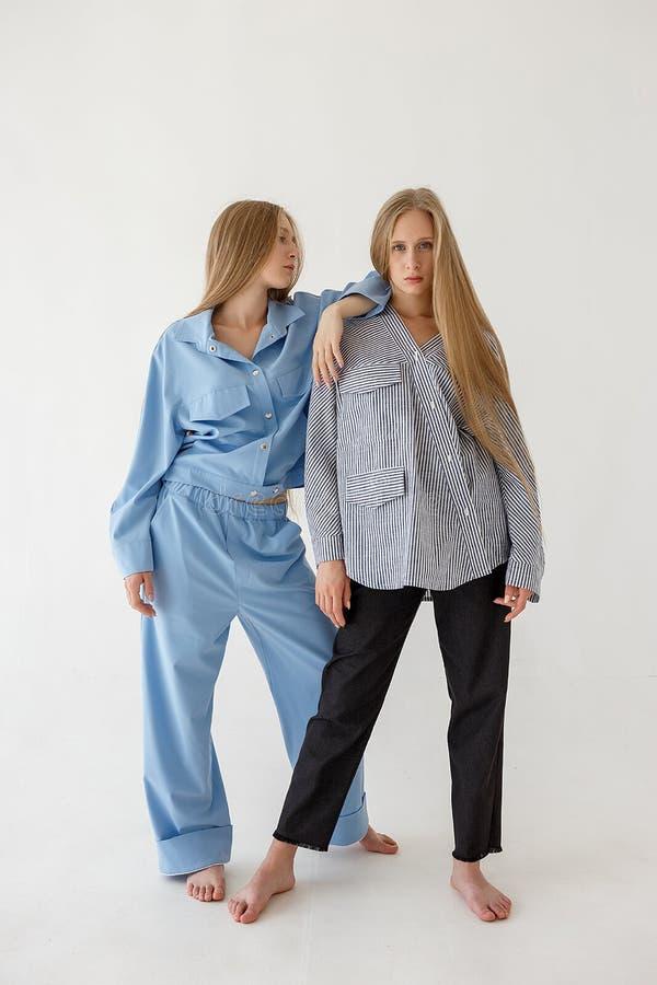 Dos hermanas gemelas bastante jovenes con el pelo rubio largo que presenta en el fondo blanco en ropa de gran tamaño Photoshoot d imagen de archivo libre de regalías
