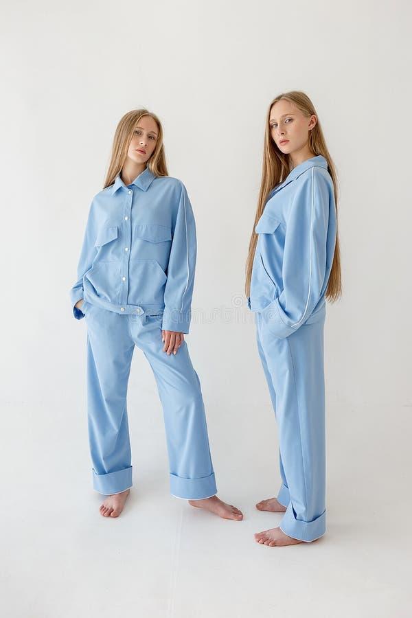 Dos hermanas gemelas bastante jovenes con el pelo rubio largo que presenta en el fondo blanco en ropa de gran tamaño Photoshoot d imagenes de archivo