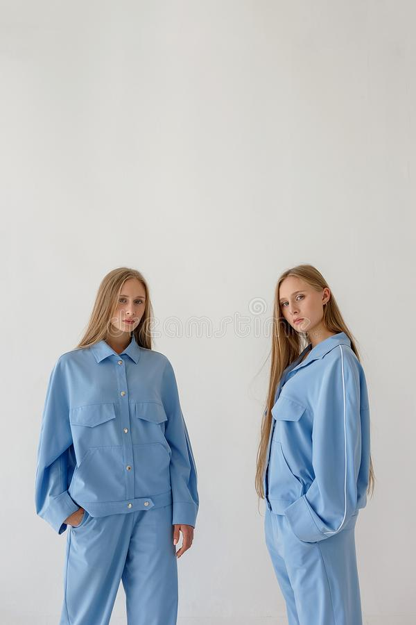 Dos hermanas gemelas bastante jovenes con el pelo rubio largo que presenta en el fondo blanco en ropa de gran tamaño Photoshoot d fotos de archivo libres de regalías