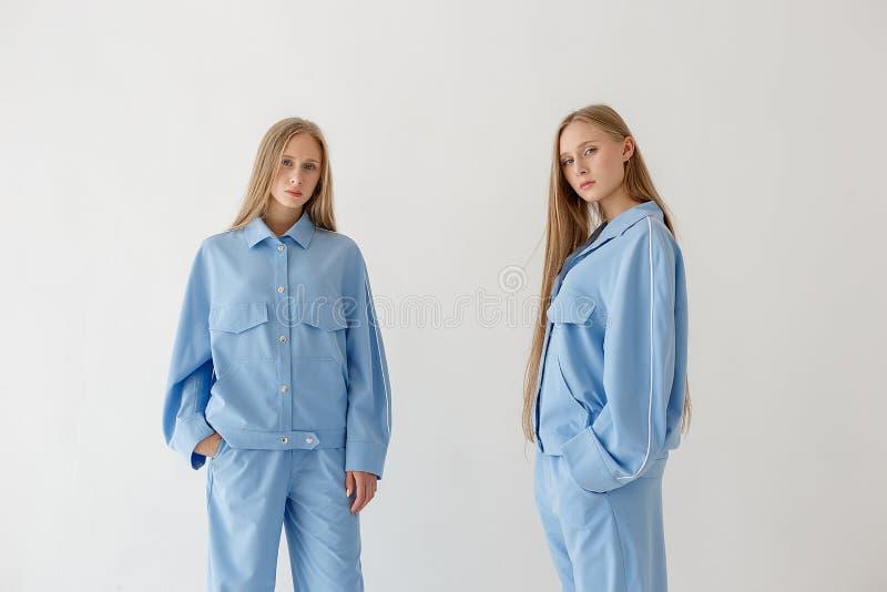 Dos hermanas gemelas bastante jovenes con el pelo rubio largo que presenta en el fondo blanco en ropa de gran tamaño Photoshoot d imagen de archivo