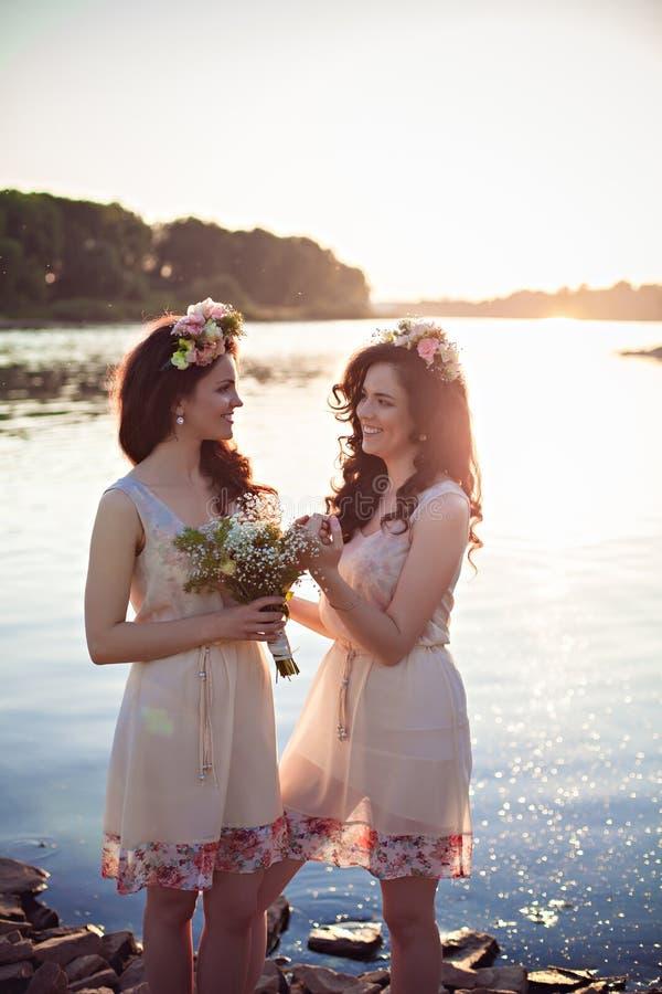 Dos hermanas hermosas en los rayos de la puesta del sol imágenes de archivo libres de regalías