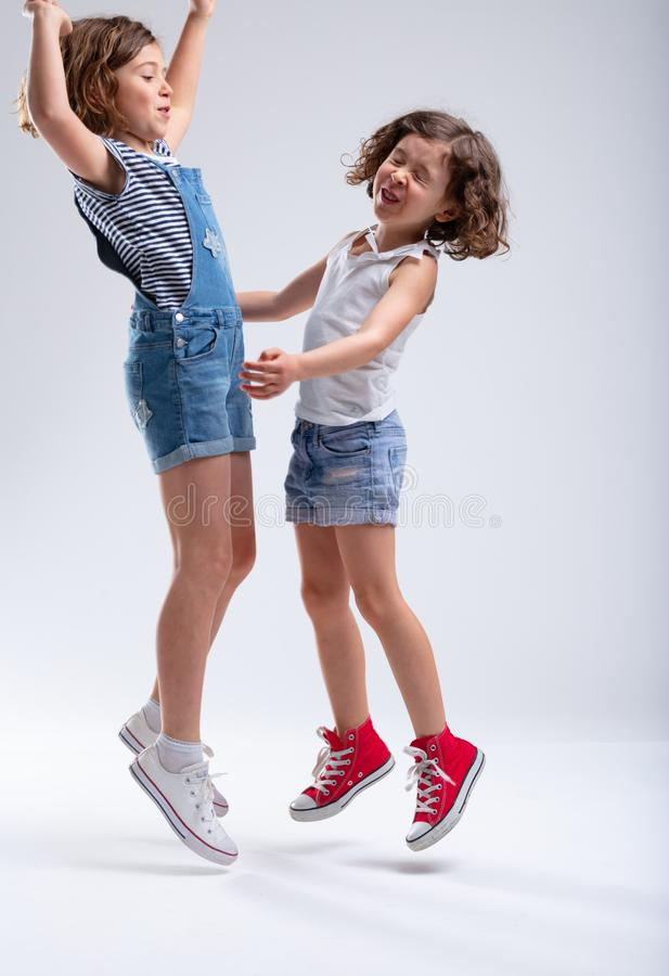 Dos hermanas jovenes que saltan y que ríen imágenes de archivo libres de regalías