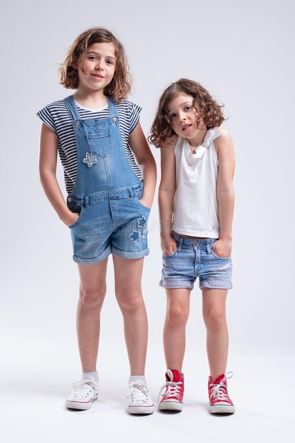 Dos hermanas jovenes que se colocan con las manos en bolsillos imagenes de archivo