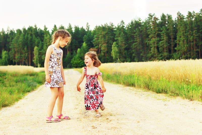 Dos hermanas lindas que corren en un campo herboso verde con sonrisas en sus caras Niños que pasan el tiempo junto al aire libre imagenes de archivo