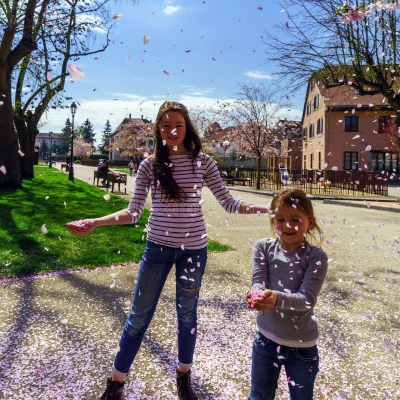Dos hermanas que juegan con los pétalos que caen en el sol imagen de archivo
