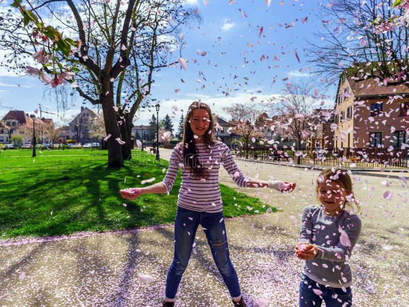 Dos hermanas que juegan con los pétalos que caen en el sol imagen de archivo libre de regalías