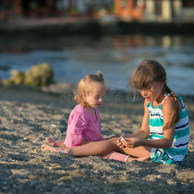Dos hermanas que juegan en la playa imagen de archivo